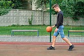 Outdoor portrait of teenage boy playing street basketball, copy space