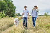 Teens walking with white dog in meadow on sunny day