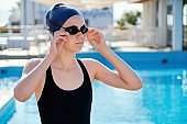 Portrait of teenage girl swimmer, outdoor swimming pool background