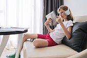 Girl studies online at home, child with digital tablet in headphones