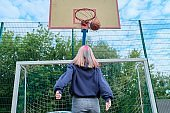 Teenager girl jumping with ball playing street basketball, back view