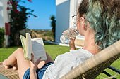 Teenager girl resting lying in an outdoor chair on lawn, reading book, drinks water from bottle