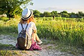 Happy teenager girl in hat with backpack sitting on country road, enjoying summer vacation