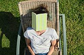 Tired teenager student asleep on sunbed with book