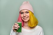 Young teenager girl with green vegetable smoothie drink