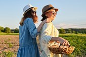Women mother and daughter with basket of eggs, lifestyle, nature, garden background