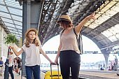 Happy mother and daughter child walking together at railway station with suitcase