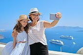 Mother and little daughter traveling together in Mediterranean, Greece, Santorini island