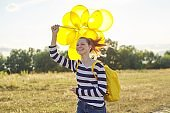 Happy teenager girl with balloons running and jumping along country road