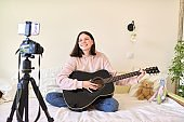 Teenage girl with acoustic guitar sitting at home on bed