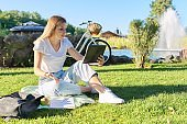 Teen girl student sitting with notebook digital tablet on green grass lawn in park