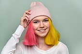 Portrait of trendy teenager girl with colored dyed hair in knitted hat