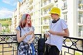 Cheerful talking students teenagers in city drinking milk yogurt from bottle