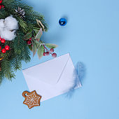 New Year's concept with a Christmas tree and Christmas decorations, a white envelope for a letter on a blue background lies nearby. there is a gingerbread and a feather on the envelope. Flat lay, copy space