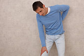 Man with neck and lower back pain, Sport injury. Pain Relief and Health Care Concept.