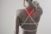 Woman suffering from back and neck pain. Chiropractic concept. Exercising injury