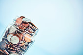 Change Jar Filled with Coins on Bright Blue Background