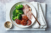 Marinated tempeh in smoky bbq sauce marinade or teryaki tempeh with rice and steamed broccoli