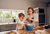 Little sisters enjoying making dough with eggs for baking in modern messed up kitchen