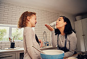 Playful mother and daughter preparing food while playing with flour in modern kitchen at home