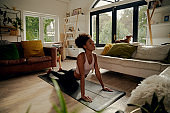 African woman lying on yoga mat at home doing stretching exercise