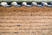 Wall of traditional Korean house made of yellow clay and tile roof.