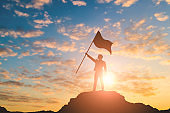 Silhouette of victory businessman on mountain with city light background. Business success and leadership concept.
