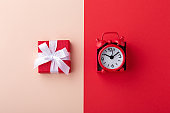 Gift box and red clock on pink and red background