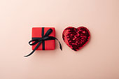 Red gift box and glitter heart, top view
