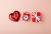 Glitter heart with red clock and gift box on pink background