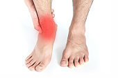 Ankle Pain man sitting on wooden background holding her feet. Health concept.