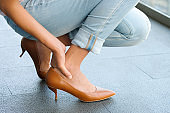 Woman sitting on road Catch her foot and she has foot pain. Caused by wearing high heels .Health and beauty concepts