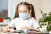 Little Girl in a Protective Mask at Distance Home Schooling, Quarantine
