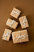Christmas gift boxes wrapped with brown kraft paper over brown background. Top view.