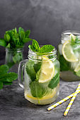 Two glasses of ice tea with fresh mint, lemon and paper straw on dark background. Summer healthy cold drink. Alternative medicine.