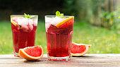 Summer refreshing drink. Two glasses of red grapefruit lemonade or cold citrus tea. Summer cold juice.