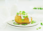 Baked potatoes with cheese, served with sour cream and onions. Selective focus