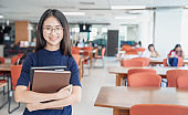 Back to school education knowledge college university concept, Beautiful female college student holding her books smiling happily standing in library, Learning and education concept