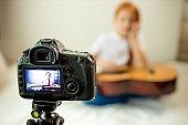 beautiful cute caucasian child blogger play guitar at camera