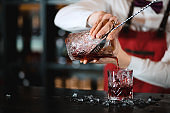 Barman pouring fresh cocktail from shaker into the glass on the bar counter