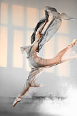 Young ballet dancer jumping on a light smoky background.