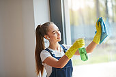 Beautiful young girl in yellow gloves stand washing window