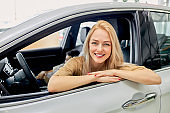 smiling lady inside of car in dealership