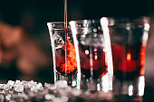 Red cocktail shots in glass isolated on blurred restaurant background.