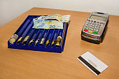Money Euro, payment terminal and credit card on the desk.