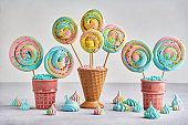 Colorful meringue lollipop in ceramic cone. Closeup with copy space