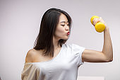 Asian woman with dumbbells, shows her strength, training biceps, isolated.