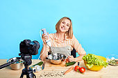 Joyful housewife broadcasting video for personal account, making vegetarian meal