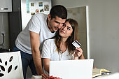 Young happy couple using laptop doing online shopping sitting at home on weekend together