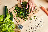 Female hands making vegetarian salad, cutting scallions on wooden board